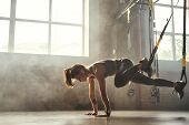 Trx Training. Young Athletic Woman In Sports Clothing Training Legs With Trx Fitness Straps In The G poster