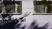 Two Windows Protected By White Gratings And Light Blue Violet Rough Wall With Blurry Shadows Created poster