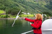 Woman In Red Jacket Traveling On Ferry Boat And Feeding Seagull. Young Woman Feeding Seagulls Flying poster