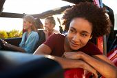 Millennial African American woman on road trip with friends, leaning out of the car window, close up poster
