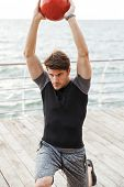 Picture of a handsome concentrated young sports man outdoors at beach make exercises with ball. poster