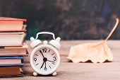 Back To School Background With Books, Clock And Fallen Leaf On A Wooden Table Over Blackboard poster