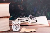 Back To School Background With Books, Clock, Fallen Leaf, Open Book And Glasses On A Wooden Table Ov poster