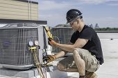 Hvac Technician Wearing Safety Gear Inspecting An Air Conditioner poster