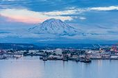 A View Of Mount Rainier And The Port Of Tacoma At Twilight. poster