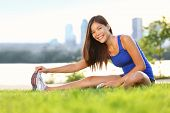Exercise woman stretching hamstring leg muscles during outdoor running workout. Smiling happy mixed