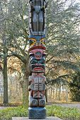 image of indian totem pole  - Totem pole on background of green and yellow trees - JPG