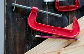 Close Up View Of Red Clamp Tool For Wood Crafting Work That Is Put On Wood Table With Pencil And The poster