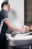 Young Woman Washing Hair In Salon. A Young Woman Is Given Scalp Massage In A Beauty Salon. poster