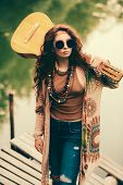 Beautiful hippie girl holding a guitar on his shoulders in the countryside. Contemporary bohemian st poster