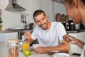 Multiethnic young couple eating cereals and drinking milk for breakfast at home. Laughing man enjoyi poster