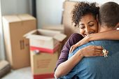 Young african woman holding home keys while hugging boyfriend in their new apartment after buying re poster