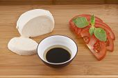 fresh mozzarella on chopping board with tomato basil