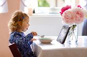 Adorable Toddler Girl Eating Healthy Cereal With Milk For Breakfast And Watching Cartoons On Tablet  poster