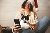 Cute Cat Looking At Phone Screen With Funny Emotions And Sitting On Happy Girl Legs In Christmas Lig poster