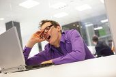 image of boredom  - bored yawning businessman working with laptop supporting his head on his hand in office space - JPG
