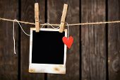 Blank instant photo and small red paper heart hanging on the clothesline. On old wood background.