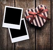 Blank instant photo frames with heart shaped Valentines Day gift box on old wooden background.