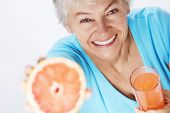 Happy elderly woman with grapefruit on white background