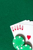 Royal Flush poker card sequence near chips on a green table. Risky entertainment of gambling