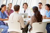 stock photo of coat  - Medical Team Discussing Treatment Options With Patients - JPG