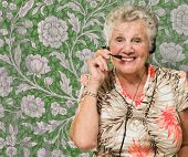 Portrait Of Cheerful Senior Woman With Telephone Headset Against Wallpaper