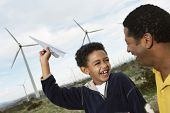 Mature man looking at son playing with paper plane at wind farm