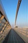 image of calatrava  - Reggio Emilia bridge by Calatrava detail showing curved hoop design and suspension wires and oncoming truck with pedestrian sidewalk second bridge beyond against blue sky at sunset Emilia Romagna Italy - JPG