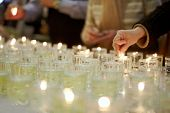 stock photo of synagogue  - Hands lighting funeral candles - JPG