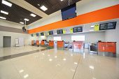 Empty terminal at airport, orange interior decoration, displays with information for passengers.