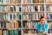 stock photo of single woman  - Portrait of clever student with open book reading it in college library - JPG