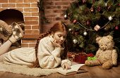 redhair woman reading book on Christmas in front of tree