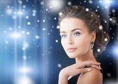 jewelry, luxury, vip, nightlife, party concept - beautiful woman in evening dress wearing diamond ea