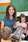 Portrait of happy preschool teacher with children playing xylophone in kindergarten