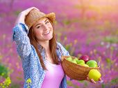 Closeup portrait of pretty woman with apples basket, having picnic on pink floral meadow, harvest se