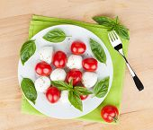 Caprese salad plate on wooden table
