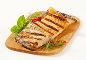 one grilled carp steak with herbs served on a wooden cutting board