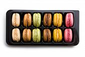 colorful macaroons in plastick box on white background
