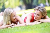 Portrait of two girls who are having pretty much fun in the park. They are talking, discussing, laug
