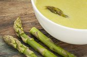 a bowl of asparagus cream soup with green asparagus spears