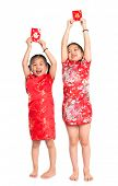 Happy Asian children holding red packet during Chinese New Year, with traditional Cheongsam full len