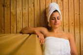 stock photo of sauna  - Calm woman relaxing in a sauna wearing white towels - JPG
