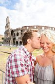 Couple kissing in love in Rome by the Colosseum. Romantic couple tourists having fun on holidays vac