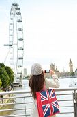 London Tourist taking picture of river Thames with London Eye, Big Ben and Palace of Westminster. Wo