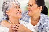 stock photo of close-up middle-aged woman  - cheerful middle aged mother and young adult daughter looking at each other - JPG