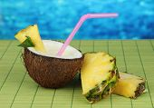 Pina colada drink in coconut, on bamboo mat, on bright background