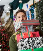 Young man looking away while carrying stacked Christmas gifts in store