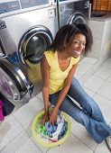 image of laundromat  - Portrait of young African American woman with laundry basket sitting at laundromat - JPG