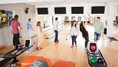 Group of happy friends playing in bowling alley