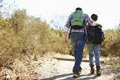 Rear View Of Father And Son Hiking In Countryside